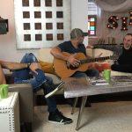 Three guys talking holding guitar